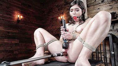 Связанная Кейра Крофт прижимает к клитору вибратор, пока пизду трахает секс машина